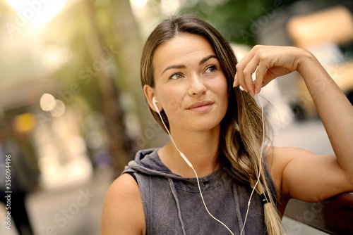 Canvastavla Attractive woman in relaxed clothing  and earbuds looking out and thinking
