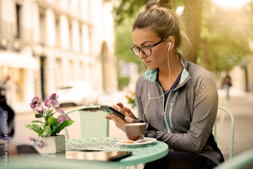Woman sitting outside of a coffee shop with headphones Fototapet