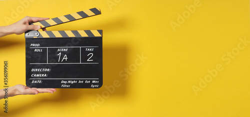 Fotografía A Hand is holding Black clapperboard or movie slate on yellow background