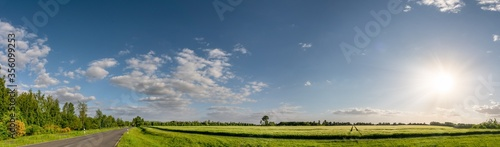 cloudy blue sky over green fields in spring with beautiful bright sun rays
