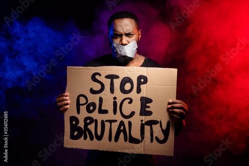 Obraz na plátne Photo of afro american revolt activist guy hold banner stop police brutality suf