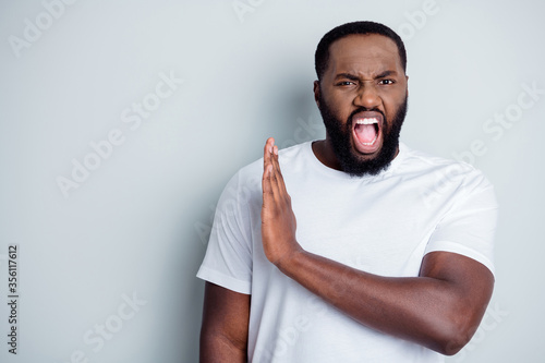 Fototapeta Photo of crazy disappointed yell dark skin african guy antiracism group member leader say no violence behavior black lawlessness raise arm empty space unfair isolated grey color background obraz