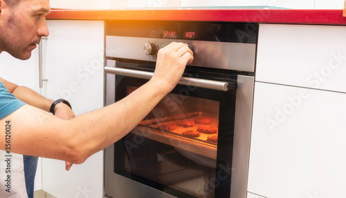 Fotografia Young man connecting the oven to make cookies