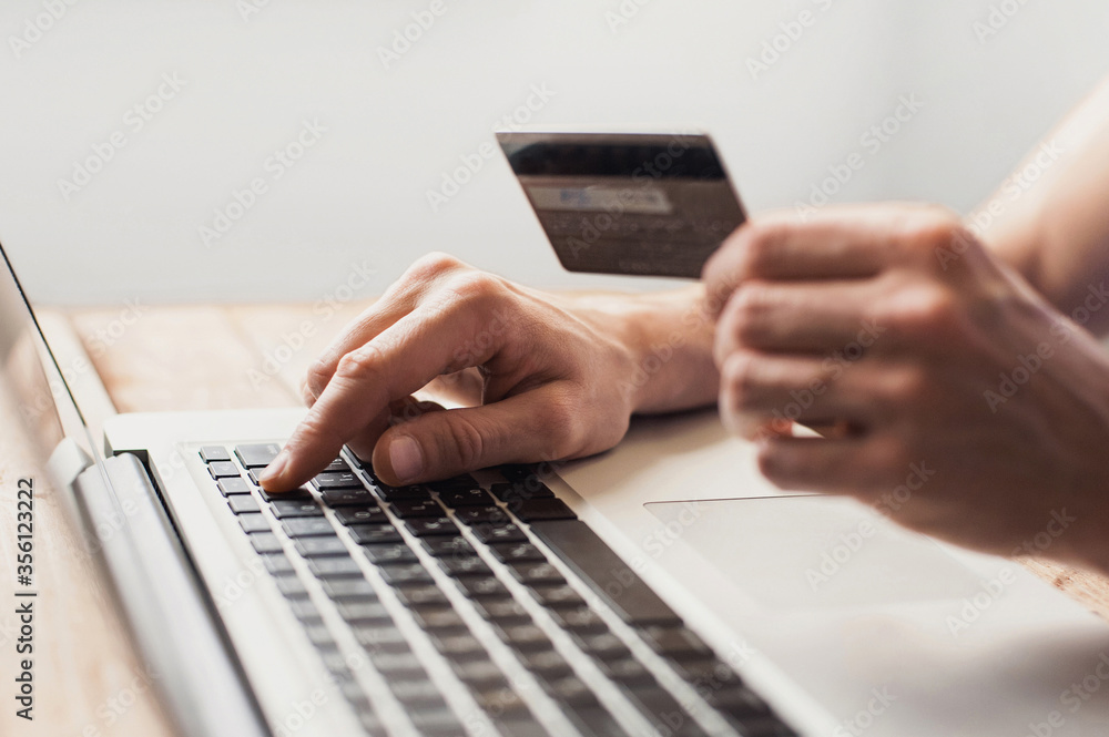 Fototapeta Man hand holding credit card and using laptop at home, Businessman or entrepreneur working, Online shopping, e-commerce, internet banking, spending money, working from home concept