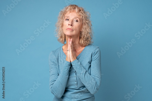 Obraz Middle aged caucasian woman holds hands together praying having sincere request, waiting for miracle - fototapety do salonu