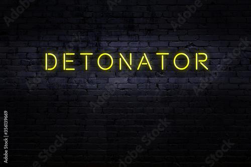 Fotografia Neon sign. Word detonator against brick wall. Night view