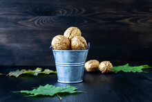 Bucket With Golden Walnuts On A Wooden Background. Conceptual Photo