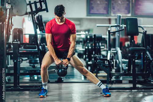Foto Young handsome man doing exercises in gym