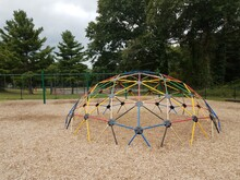 Colorful Metal Jungle Gym On Playground With Wood Chips