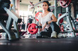 Asian women with beautiful tan skin sit and relax at the exercise bench. After sports training with dumbbells For health in the fitness center Concept: sporty girls sitting in the gym