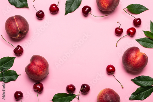 Obraz Pink summer background with frame of ripe peaches and cherries, copy space - fototapety do salonu
