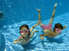 Children Swim In Swimming Pool Underwater, Happy Active Kids Have Fun Under Water, Fitness And Sport On Active Family Vacation