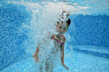 Child Swims In Pool Underwater, Happy Active Girl Jumps, Dives And Has Fun Under Water, Kids Fitness And Sport On Family Vacation