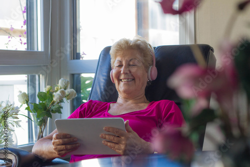 Photo Grandmother listening to funny news on one of her devices through the internet