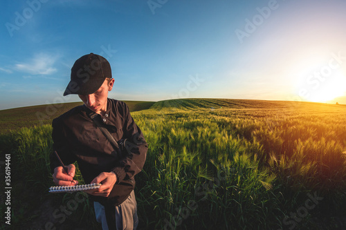 Fototapeta Young agronomist in cap takes notes in a notebook on a green agricultural field during sunset obraz