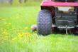 Leinwanddruck Bild - Gardening concept background. Gardener cutting the long grass on a tractor lawn mower