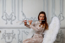 Woman With Flute. Girl Actress In Suit With Flute On Light Background. Flute In Hand. Concept Of Musical Design. Author's Space. Large Background Space For An Inscription Or Logo