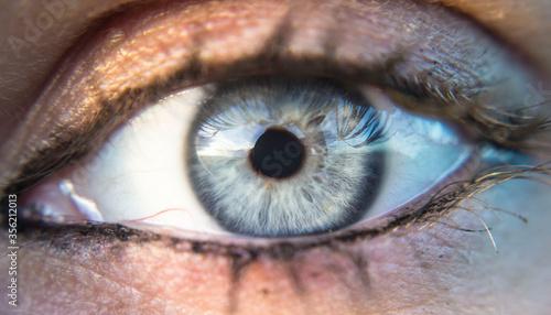 Tela detalle de ojo azul intenso con mancha en el iris con maquillaje