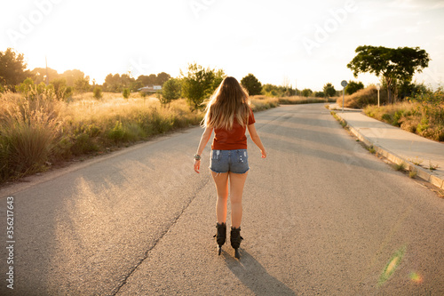 Chica rubia haciendo patinaje en línea por la carretera al atardecer durante el Canvas Print