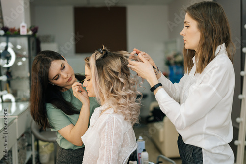 Photo Professional female hairdresser make-up artist making hairstyle Caucasian model blonde in dressing room