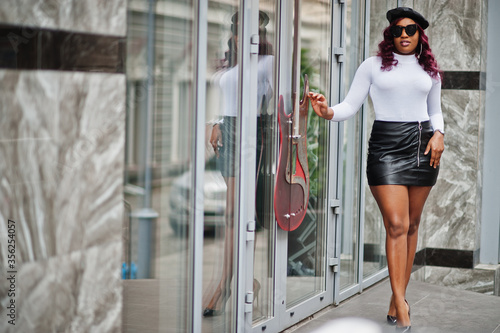 Obraz na plátně Big mama plus size african american model in black sunglasses, beret and leather skirt posed outdoor