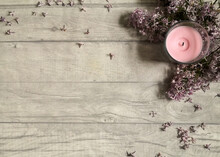 Pink Candle With Lilac Flowers On Wooden Surface Shot From Above. Top View, Flat Lay, Copy Space.  Relaxing At Home And Hygge Composition. Space For Text.