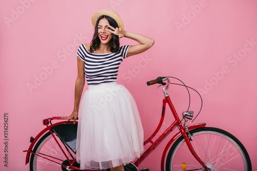 Fotografia, Obraz Stunning latin girl in lush skirt standing near red bicycle