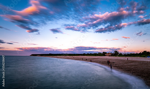 Wide beach landscape with mountains and smooth water Canvas Print