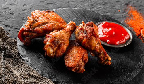 Photo Grilled chicken wings and legs meat with tomato sauce on slate board over dark background