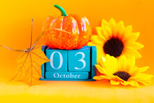 October 3. Wooden Cube Calendar With Month And Date On Bright Orange Background