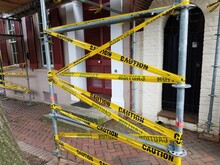 Construction Scaffolding With Yellow Warning Tape And Bricks