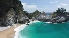 4K Aerial View Of The Empty Secluded Beach With Beautiful Scenic Cove, Sea Cliffs And Amazing Color Clear Ocean. Charming Waterfall Reveals Behind The Sheer Cliff. Great Nature Of The Pacific Coast
