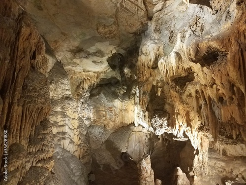 brown stalactites and stalagmites in cave or cavern