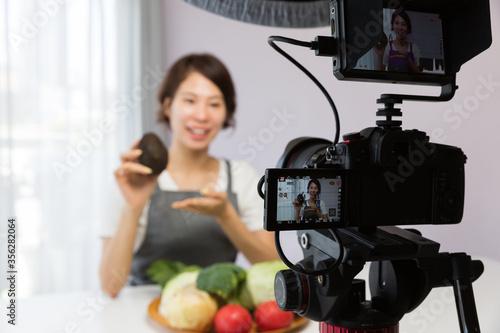 Fototapeta 一眼レフカメラで動画を撮影する女性 obraz