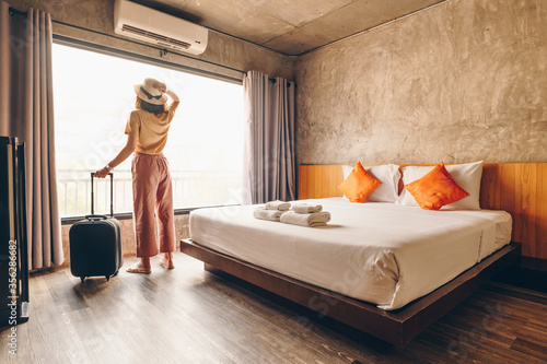 Portrait of tourist woman standing nearly window, looking to beautiful view with her luggage in hotel bedroom after check-in Wallpaper Mural