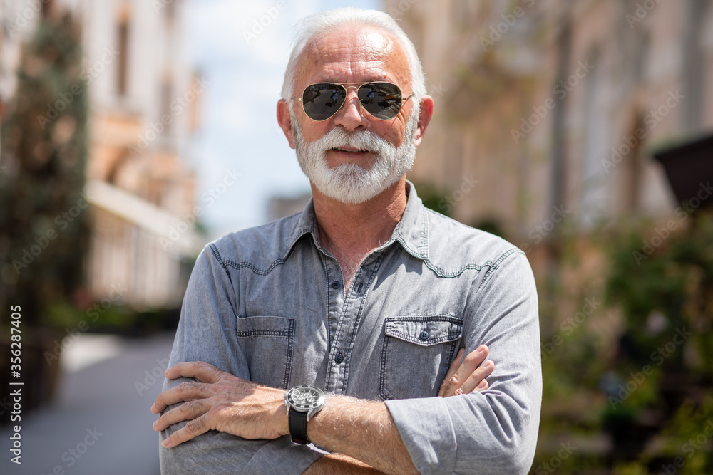 Fototapeta Old rich man with sun glasses and beard on street portrait