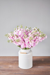 Bouquet of Beautiful lilac mattiola. Spring flowers in vase on wooden table. Flowers delivery.