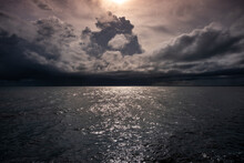 Low Key Image Of Sunset Over The Sea With Dramatic Sky With Clouds Under Sunlight