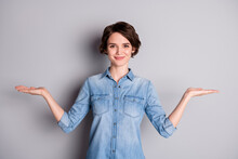 Photo Of Attractive Lady Hold Open Arms Hands Empty Space Showing Nice Offer Two Variants Pick Select Best One Wear Casual Denim Shirt Isolated Grey Color Background