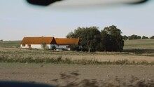 Views On A Roadtrip In Southern Sweden Vacation On A Small Farm With Classical White Buildings And Orange Roofing Surrounded By Crops Farmlands Agroculture Seen From Inside A Car Interior On A Road