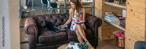 Fototapeta Businesswoman working with laptop sitting on the sofa in a coworking office obraz