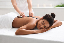 Relaxed African Woman Getting Hot Stone Massage At Spa