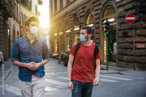 Fotomural Two young friends meet in the city wearing protective masks from the Corona viru