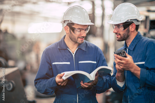 Obraz na plátně Engineer team talking together teach and learn engineering technical about using machine with open instruction manual text book in factory workplace