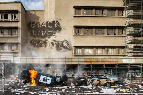 Black Lives Matter protest riot vandelism, looting aftermath concept, flaming police car smashed, overturned with black lives matter text slogan message on building Canvas Print