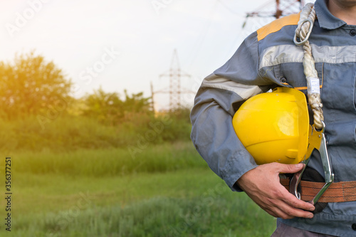 Fotomural A young electrical engineer, with a protective helmet in his hands, against the background of a power line