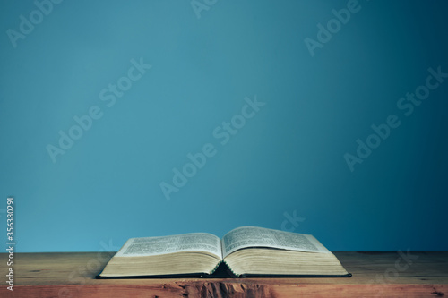 Fototapeta Open Holly Bible on a red wooden table. Beautiful blue wall background. Religious concept. obraz