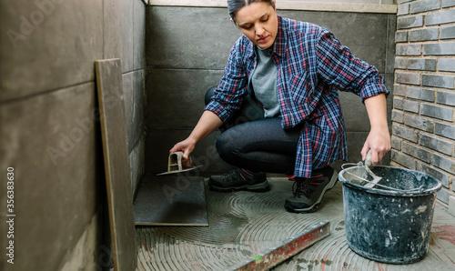 Cuadros en Lienzo Female mason laying a new tile floor on a terrace