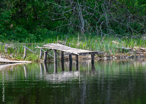 Fotografiet landscape with an old wooden footbridge in a small forest lake