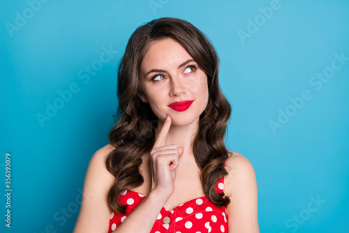 Fototapeta Closeup photo of attractive curly lady minded good mood arms crossed look up empty space interested creative arm on chin wear red dotted dress singlet isolated blue color background obraz